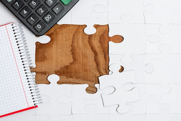 Белые кусочки пазла крупным планом, которые нужно соединить с отсутствующим последним элементом, расположенным на плоском фоне с разной текстурой и принадлежностями для бумаги