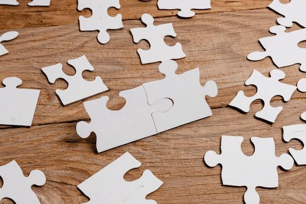 Белые кусочки пазла крупным планом, которые нужно соединить с отсутствующим последним фрагментом