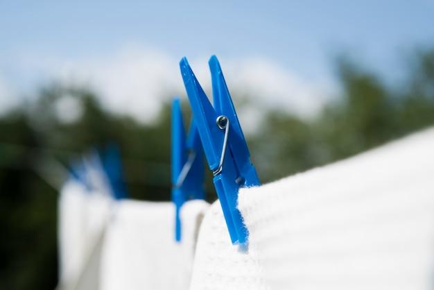 Lavanderia bianca del primo piano che appende su una corda all'aperto