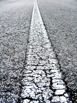 Close-up on the white line of an alphast road.