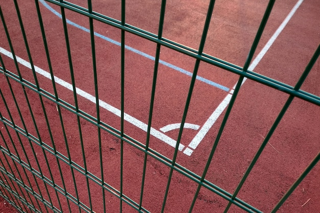 Close-up of white marking lines of outdoor basketball court fenced with protective metal fence.
