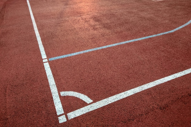 Close-up of white marking lines of outdoor basketball court.