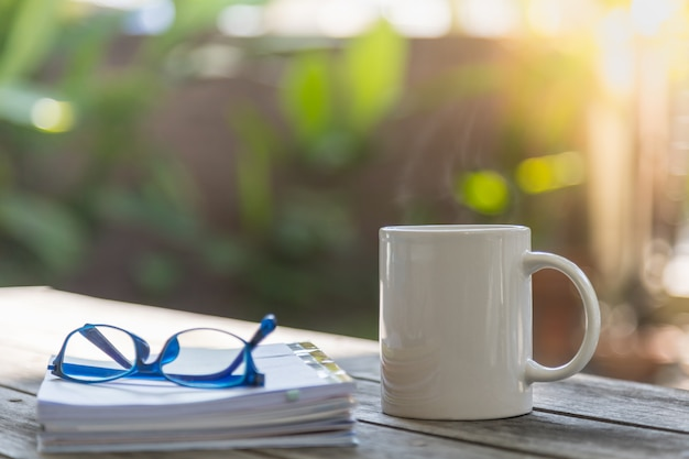 Close up of white mug cup of hot coffee with book and reading glasses on wooden table in garden with copy space.