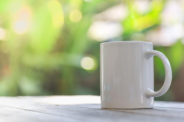 Close up of white mug cup of hot coffee on wooden table and bokeh green leaf nature under sunlight as background.