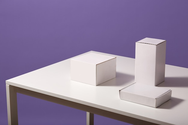 Close up of white paper carton boxes on table isolated over lilac, three blank cases on desk
