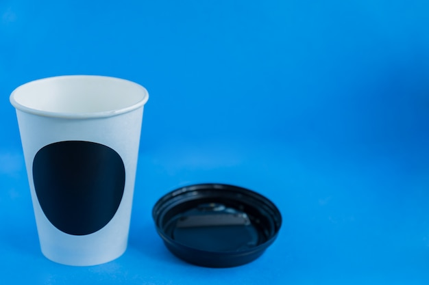 Close up of white paper kraft disposable cup for coffee with black plastic lid on blue with copy space