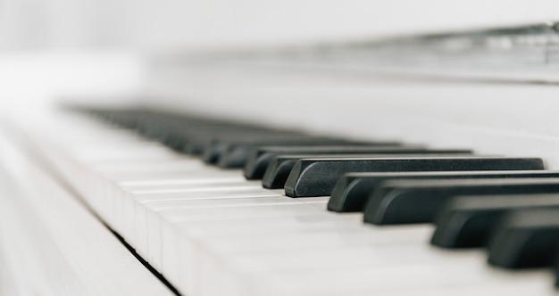 흰색 피아노 키보드를 닫습니다. 악기. 흑백 키. 소리, 화음, 멜로디를 연주합니다.
