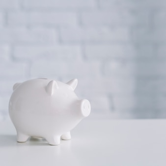 Close-up of a white piggybank on desk