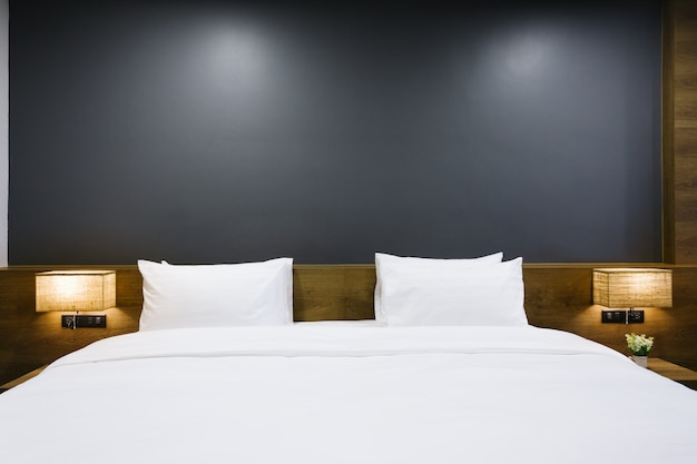 Close-up of white pillow on bed decoration with light lamp in hotel bedroom interior.