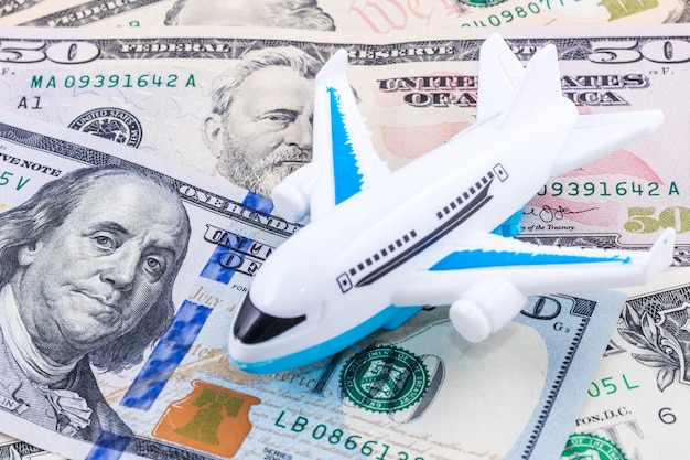 Close-up white plane toy on dollar bill.
