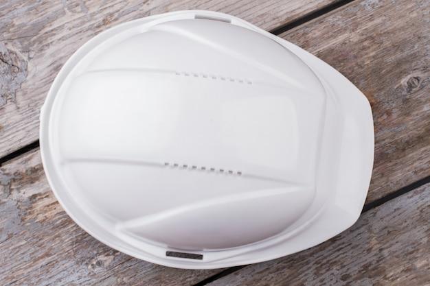 Закройте белый пластиковый шлем для строителей. крупным планом вид сверху. серый деревянный стол на заднем плане.