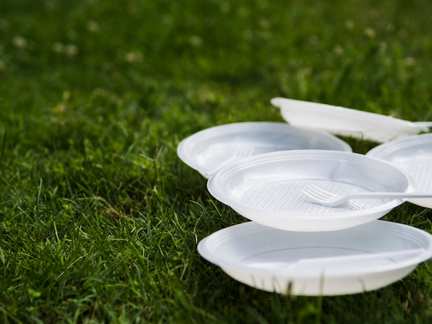 Close-up of white plastic plate and fork on grass at park