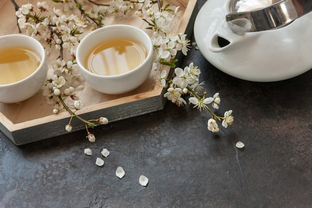 Close up of white porcelain asian tea set with green japan tea with cherry blossoming branches