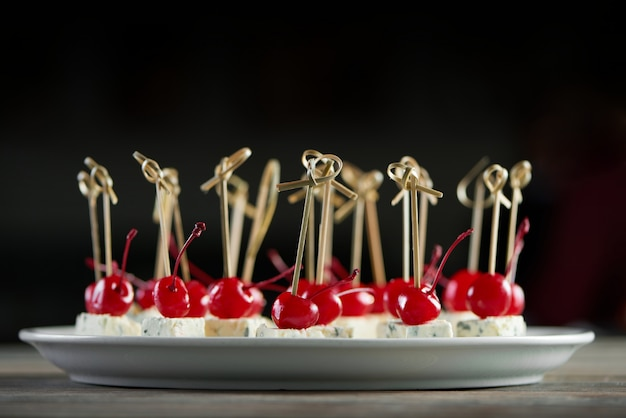 Close-up of white round plate full of delicious appetizers with red cocktail cherries and blue cheese pieces. good snack for light alcohol catering or restaurant buffet.
