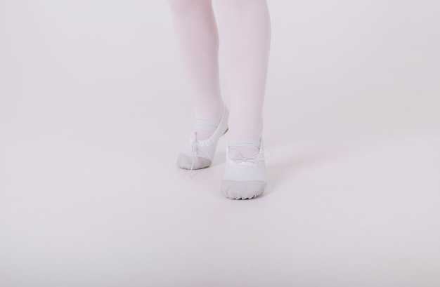Close-up of white small pointe shoes of a ballerina girl on a white wall