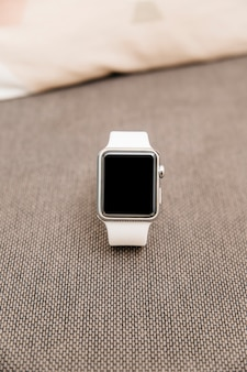 Close-up of a white smartwatch with black screen