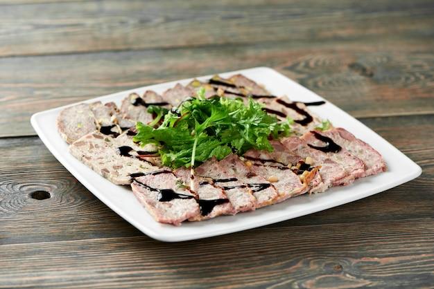 Primo piano di un piatto quadrato bianco servito con fette di carne ripiene, decorato con foglie verdi e salsa di soia sul tavolo di legno.