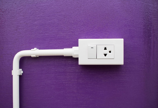 Close-up white switch and  plug on purple wall with copy space