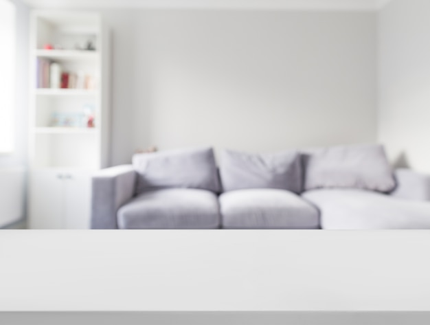 Close-up of white table in front of defocused sofa