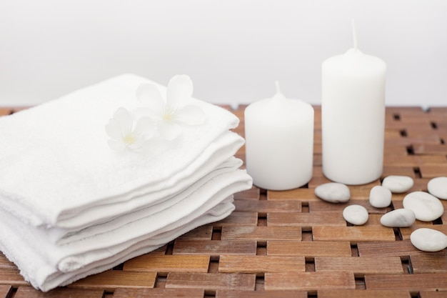Close-up of white towel; flowers; candles and pebbles on wooden table