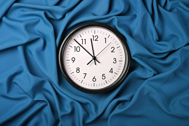 Закройте белые настенные классические часы на синем текстильном фоне со сложенными складками ткани, вид сверху, прямо над