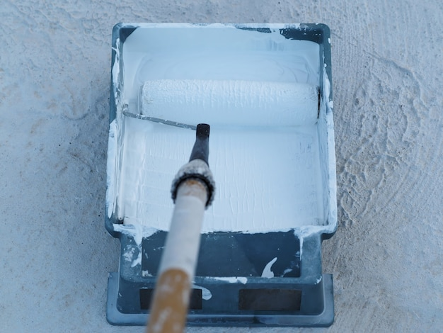 Close-up. white waterproof paint in green container and roller at rooftop