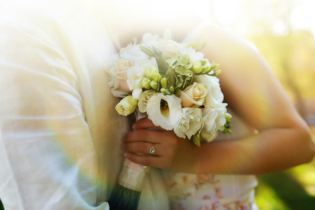 Close-up of white wedding bouquet in hands of bride hugging groom