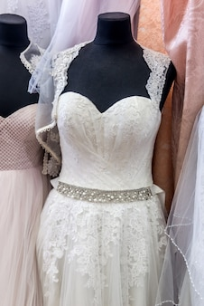 Close-up on white wedding dress on mannequin