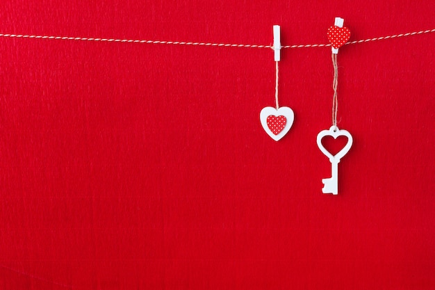Close up of white wooden heart simbol and key on red paper background.