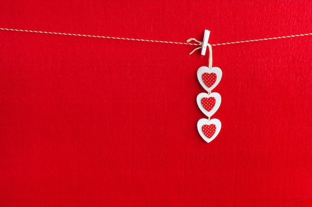 Close up of white wooden heart simbol on red paper background