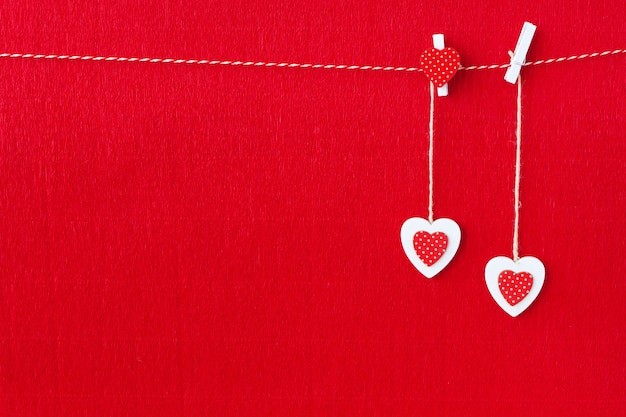 Close up of white wooden heart simbos on red paper background
