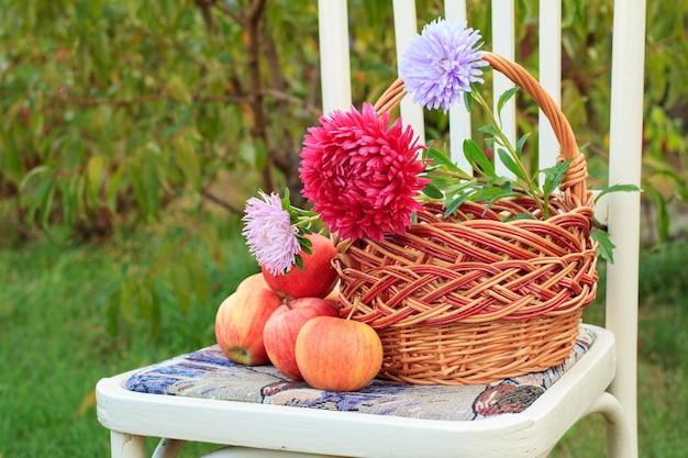Макро плетеная корзина с цветами и яблоками на белом деревенском стиле стуле в саду с зеленым естественным фоном.