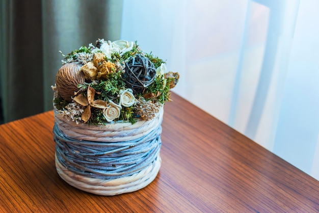 Close up of a wicker flower pot with dried flowers arrangement over a wooden table by the window.
