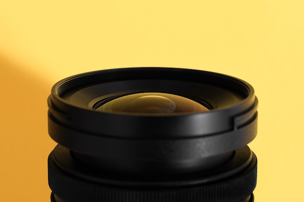 Close-up of an wide angle camera lens with glass reflections on yellow surface