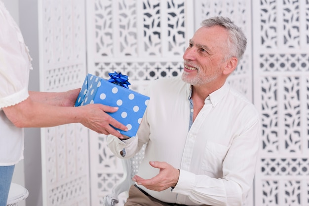 Close-up of wife giving birthday gift to her senior husband