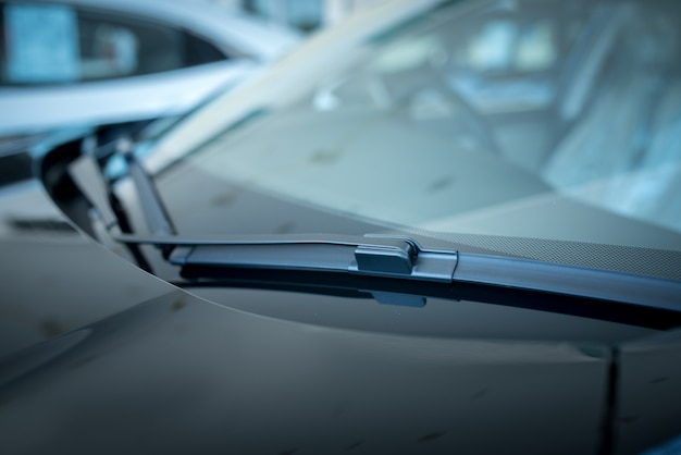 Close up of a windscreen wiper or windshield wiper is a device used to remove rain, snow, ice and debris from a windscreen or windshield. , new cars parked in the showroom