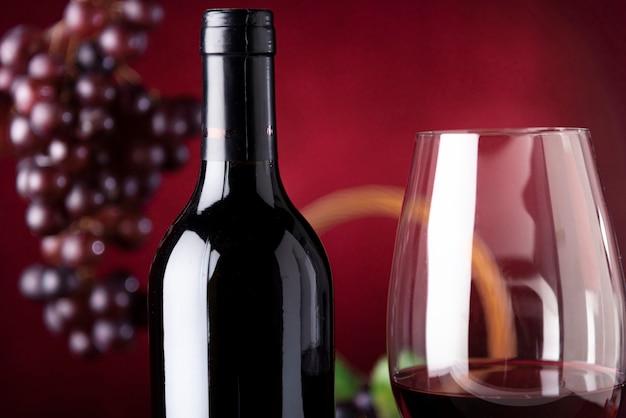 Бутылка вина крупным планом со стеклом