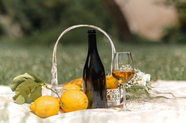 Close-up of wineglass full of white wine, an empty bottle and wine flavors around. picnic basket full of variety of tropical fruits on a picnic blanket.