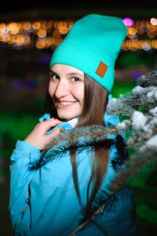 Close up winter portrait of a young smiling woman in a blue hat at night.