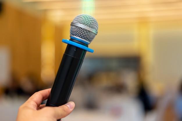 Крупным планом беспроводной микрофон в классе семинара с размытыми студентами позади
