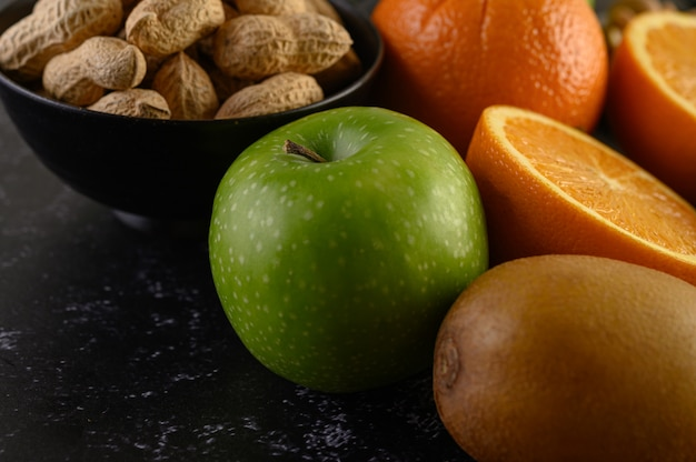 Close up with  apple, peanut, slice of fresh orang, kiwi, and avocado.