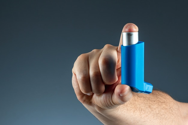 Close-up with an asthma inhaler in a male hand, asthmatic attack. the concept of treatment of bronchial asthma, cough, allergies, dyspnea.