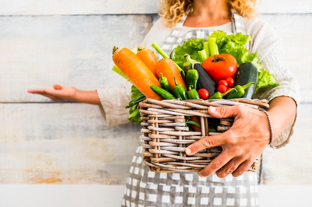 Close up with caucasian woman taking a bucket full of coloured and fresh seasonal vegetables for a healthy and natural food lifestyle - wellness and diet concept lifestyle
