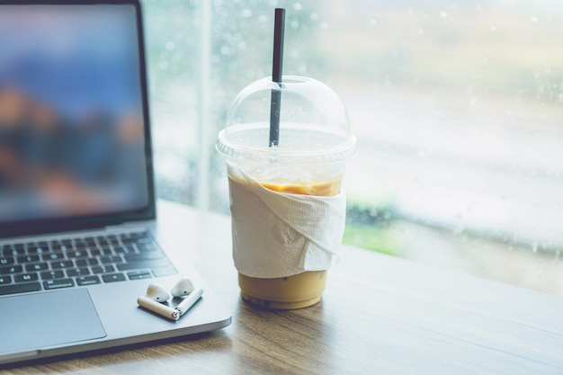 Close-up of with coffee cup working with laptop computer and earphone  with isolate on wooden background office desk in coffee shop like the background