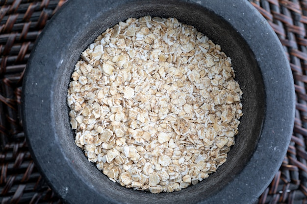 Close-up with crushed whole oats. in stone mortar. rustic appearance.