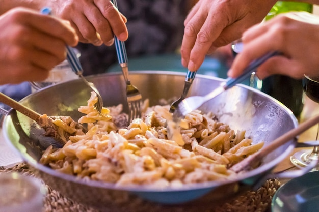 Close up with different many hands friends taking italian pasta together with the forks to have fun and enjoy the friendship. everybody eating with the same dish. home or restaurant food concept