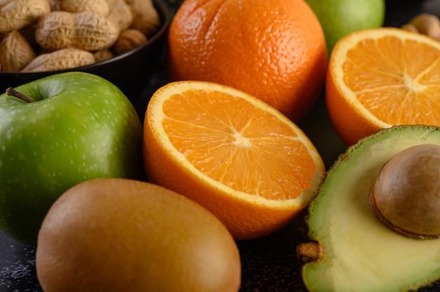 Закройте вверх с ломтиком свежего апельсинового яблока, кивиа, арахиса и авокадо.