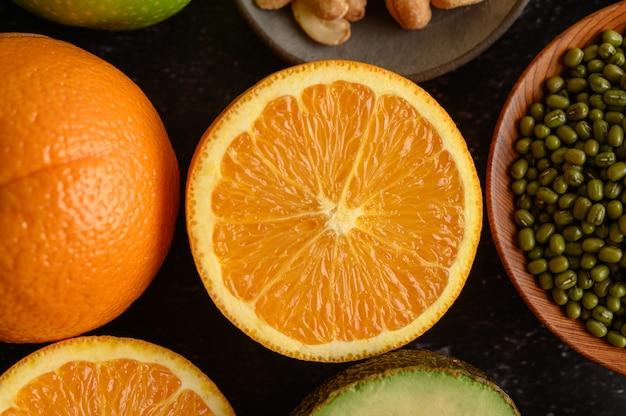 Закройте ломтик свежего апельсина, бобы мунг и авокадо.