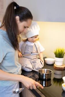 クローズアップの女性とキッチンの子供