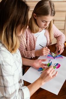クローズアップの女性と子供が蝶を描く